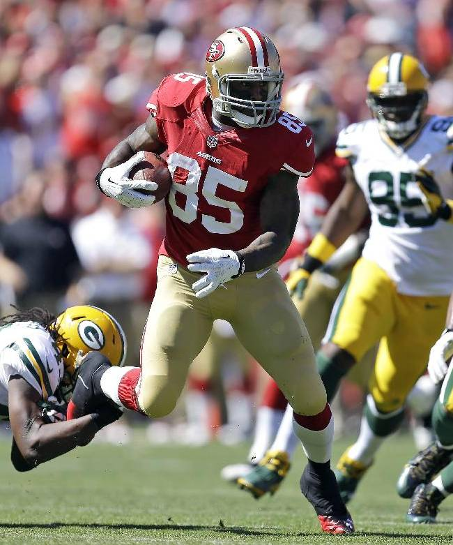 In this Sept. 8, 2013, file photo, San Francisco 49ers tight end Vernon Davis (85) runs from Green Bay Packers free safety M.D. Jennings, left, and defensive tackle Mike Neal (96) during the second quarter of an NFL football game in San Francisco. For the first time as pros, Davis could face off against his brother, Indianopolis Colts cornerback Vontae Davis, when their two teams meet on Sunday