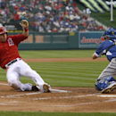 Los Angeles Angels' Mike Trout, left, slides in for a score in front of Los Angeles Dodgers catcher A.J. Ellis during the first inning of an exhibition baseball game in Anaheim, Calif., Saturday, March 29, 2014 The Associated Press