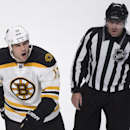 FILE - In this Thursday, Oct. 16, 2014 file photo, Boston Bruins' Milan Lucic, left, reacts as he is escorted off the ice by linesman Michel Cormier after receiving a penalty near the end of an NHL hockey game against the Montreal Canadiens, in Montreal. The NHL has fined Lucic $5,000 for making an obscene gesture at the fans in Montreal. (AP Photo/The Canadian Press, Paul Chiasson, File)