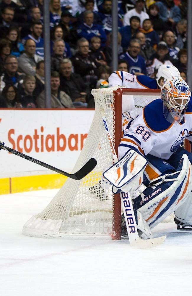 A pass by Vancouver Canucks' Jordan Schroeder, left, deflects off Edmonton Oilers' Corey Potter, right, and goes into the net for a goal past goalie Ilya Bryzgalov, of Russia, during first period of an NHL hockey game in Vancouver, British Columbia, on Monday Jan. 27, 2014