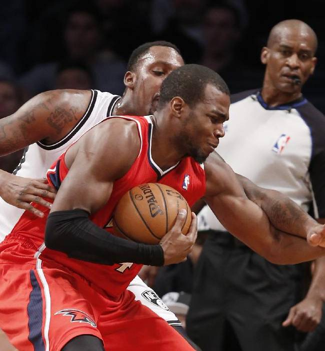 Brooklyn Nets center Andray Blatch, left, defends Atlanta Hawks Paul Millsap in the first half of their NBA basketball game at the Barclays Center, Monday, Jan. 6, 2014, in New York