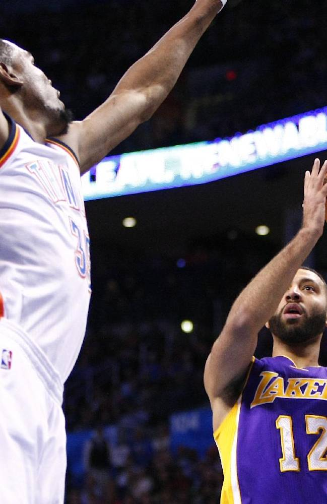 Los Angeles Lakers guard Kendall Marshall (12) shoots in front of Oklahoma City Thunder forward Kevin Durant (35) during the first quarter of an NBA basketball game in Oklahoma City, Thursday, March 13, 2014