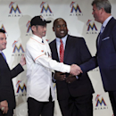 Ichiro Suzuki, second left, shake hands with Dan Jennings, right, Miami Marlins team's general manager, as Michael Hill, second right, president of Marlins' baseball operations, and Marlins president David Samson, left, accompany during a news conference