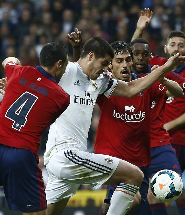Real's Alvaro Morata, second left, in action with Osasuna's Miguel Flano, left, during a Spanish La Liga soccer match between Real Madrid and Osasuna at the Santiago Bernabeu stadium in Madrid, Spain, Saturday, April 26, 2014