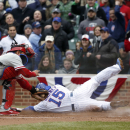 Chicago Cubs' Darwin Barney (15) slides safely into home as Philadelphia Phillies catcher Carlos Ruiz (51) tries to put the tag on him during a baseball game Friday, April 4, 2014, in Chicago The Associated Press