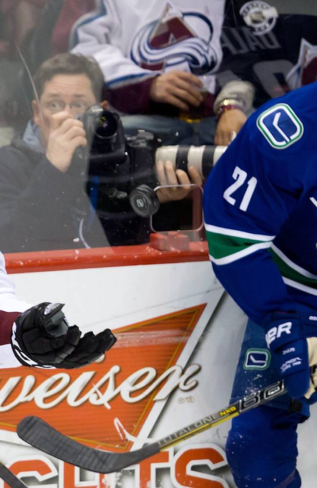 Colorado Avalanche's Marc-Andre Cliche, left, grabs the puck out of the air as Vancouver Canucks' Zac Dalpe watches during third period of an NHL hockey game in Vancouver, British Columbia, on Sunday, Dec. 8, 2013