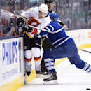 Toronto Maple Leafs defenceman Cody Franson, right, hits Calgary Flames forward Mason Raymond (21) during the first period of an NHL hockey game in Toronto on Tuesday, Dec. 9, 2014 The Associated Press