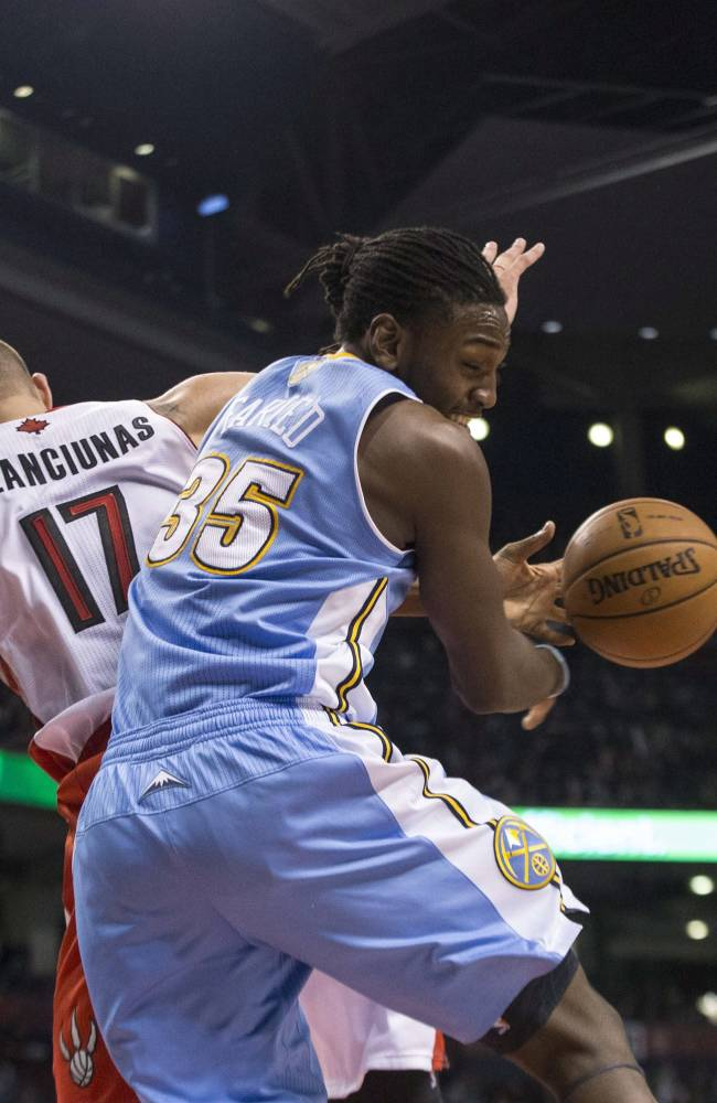 Denver Nuggets' Kenneth Faried, right, battles for a rebound with Toronto Raptors' Jonas Valanciunas during the first half of an NBA basketball game on Sunday, Dec. 1, 2013, in Toronto