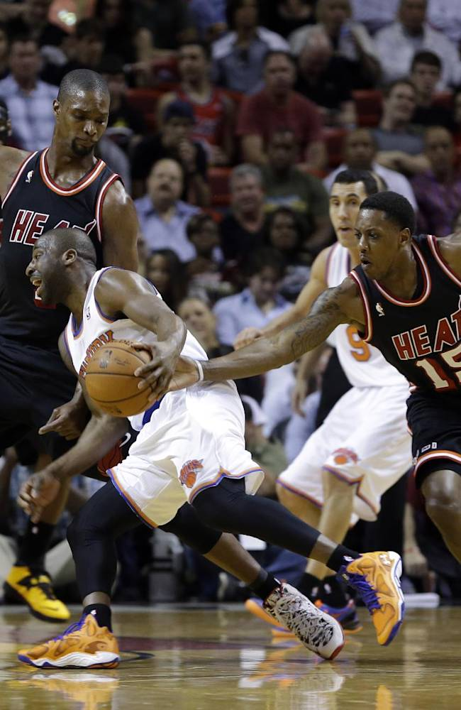 New York Knicks point guard Raymond Felton, center, drives against Miami Heat center Chris Bosh (1) as Heat's Mario Chalmers (15) defends during the first half of an NBA basketball game in Miami, Thursday, Feb. 27, 2014