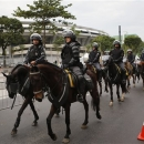 Fans, left, look as mounted police patrols the surroundings of the Maracana stadium, background, ahead of the Confederations Cup soccer final between Brazil and Spain in Rio de Janeiro, Brazil, Sunday, June 30, 2013. Security around the stadium is high as demonstrators march toward the stadium ahead of the final. Protesters have taken to the streets all over Brazil in the past two weeks, calling for a wide-range of reforms.(AP Photo/Victor R. Caivano)