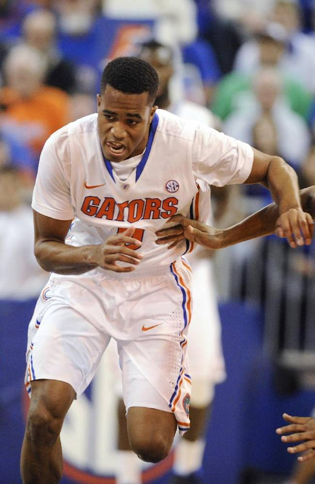 Florida's Kasey Hill (0) and Georgia's Kenny Gaines (12) chase a loose ball during the first half of an NCAA college basketball game Tuesday, Jan. 14, 2014, in Gainesville, Fla