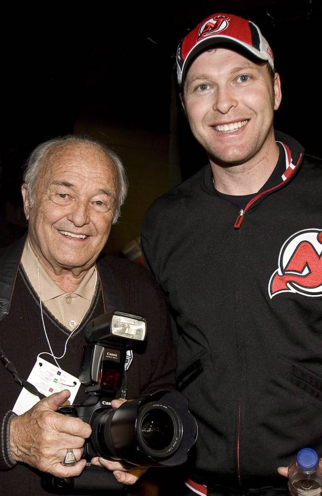 In this March 14, 2009, file photo, photographer Denis Brodeur, left, poses with his son, New Jersey Devils goaltender Martin Brodeur, in Montreal. Denis Brodeur, who enjoyed a lengthy career as one of Canada's most successful sports photographers, died Thursday, Sept. 26, 2013, the New Jersey Devils said. He was 82