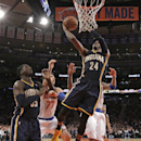 Indiana Pacers forward Paul George (24) goes up for a layup in front of New York Knicks power forward Andrea Bargnani (77) as Pacers center Roy Hibbert (55) watches from the floor in the second half of their NBA basketball game at Madison Square Garden in