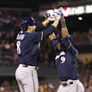 Milwaukee Brewers' Ryan Braun (8) is greeted by teammate Jean Segura (9) after driving him in with a two-run home run in the ninth inning of the baseball game against the Pittsburgh Pirates, Saturday, April 19, 2014, in Pittsburgh. The Brewers won 8-7 The