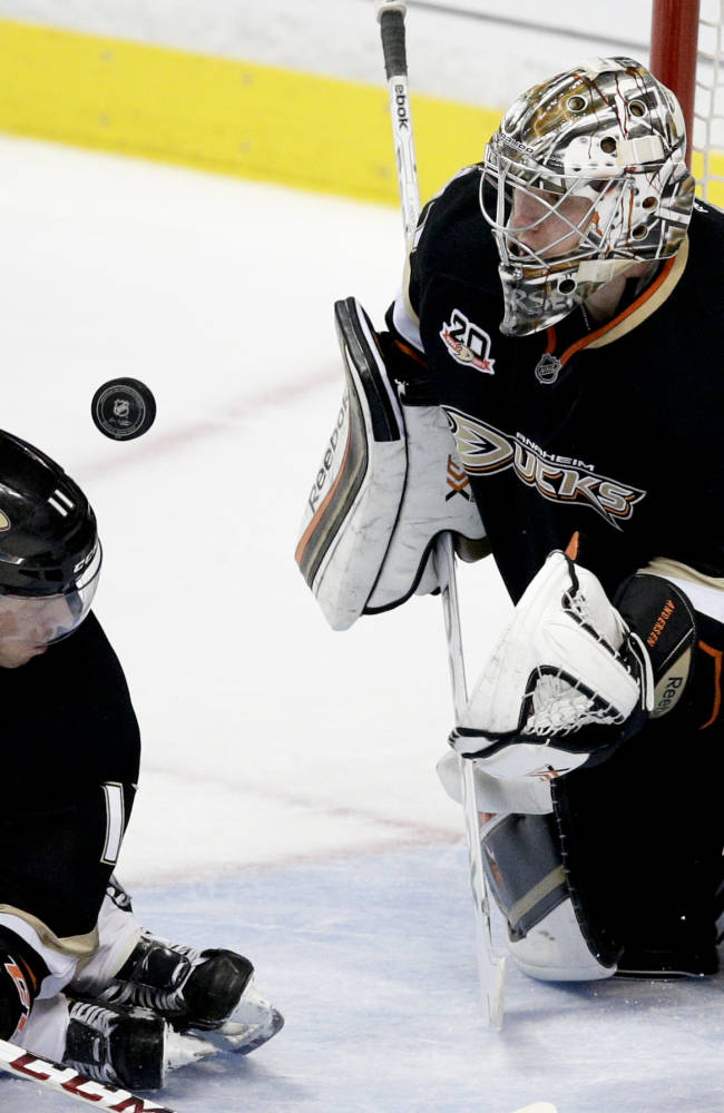 Anaheim Ducks goalie Frederik Andersen, right, of Denmark, deflects a puck in front of teammate Saku Koivu, of Finland, during the second period of an NHL hockey game against the Vancouver Canucks on Wednesday, Jan. 15, 2014, in Anaheim, Calif. (AP Photo/Jae C. Hong)