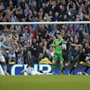 Wigan Athletic's James Perch, right, celebrates after scoring past Manchester City's goalkeeper Costel Pantilimon, center right, during their English FA Cup quarterfinal soccer match at the Etihad Stadium, Manchester, England, Sunday March 9, 2014. (AP Ph