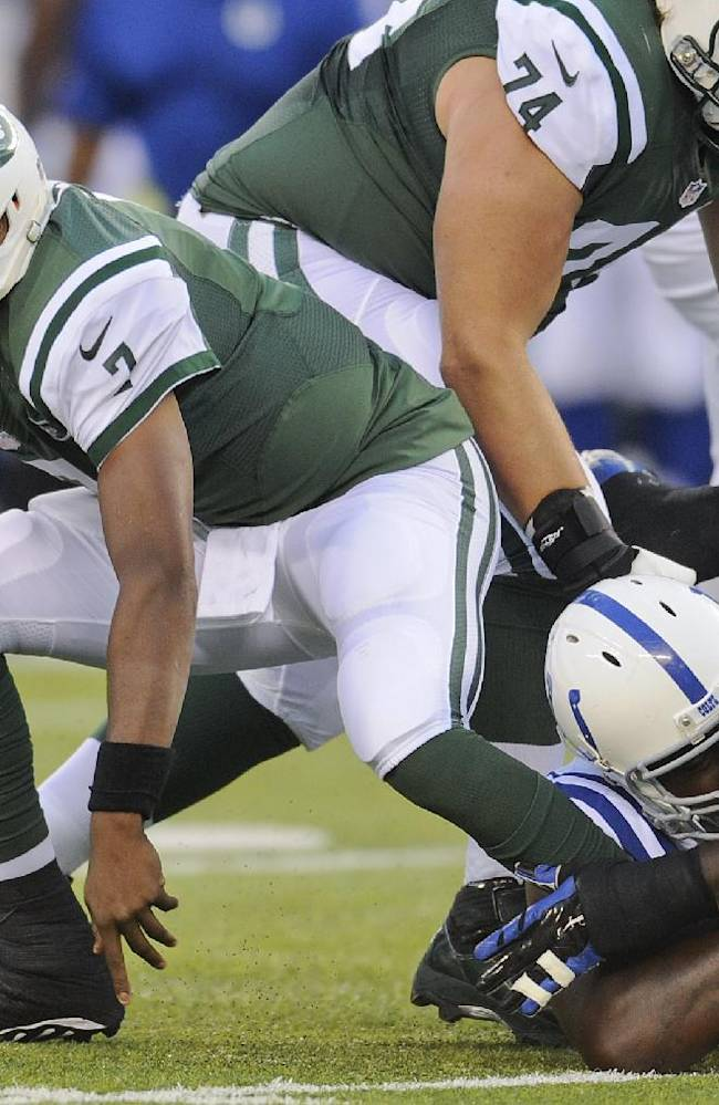 New York Jets quarterback Geno Smith (7) is wrapped up by Indianapolis Colts defensive end Arthur Jones (97) in the first quarter of an NFL football game, Thursday, Aug. 7, 2014, in East Rutherford, N.J