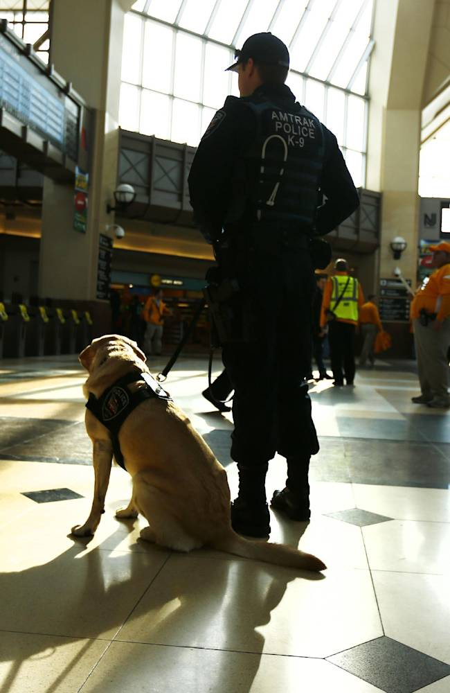 A police officer and his dog keep watch at the Secaucus Junction, Sunday, Feb. 2, 2014, in Secaucus, N.J. The Seattle Seahawks are scheduled to play the Denver Broncos in the NFL Super Bowl XLVIII football game on Sunday, earning MetLife Stadium in East Rutherford, N.J