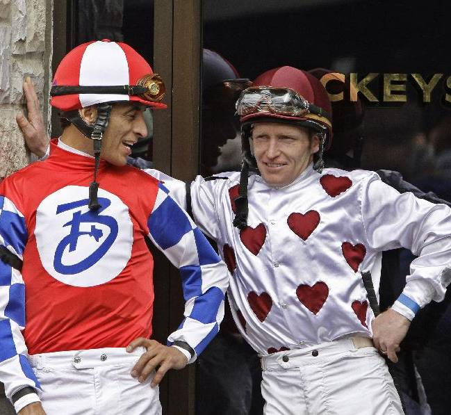 John Velazquez, left, and James Graham, right, talk outside the jockeys' quarters before a horse race on opening day at Keeneland in Lexington, Ky., Friday, April 4, 2014
