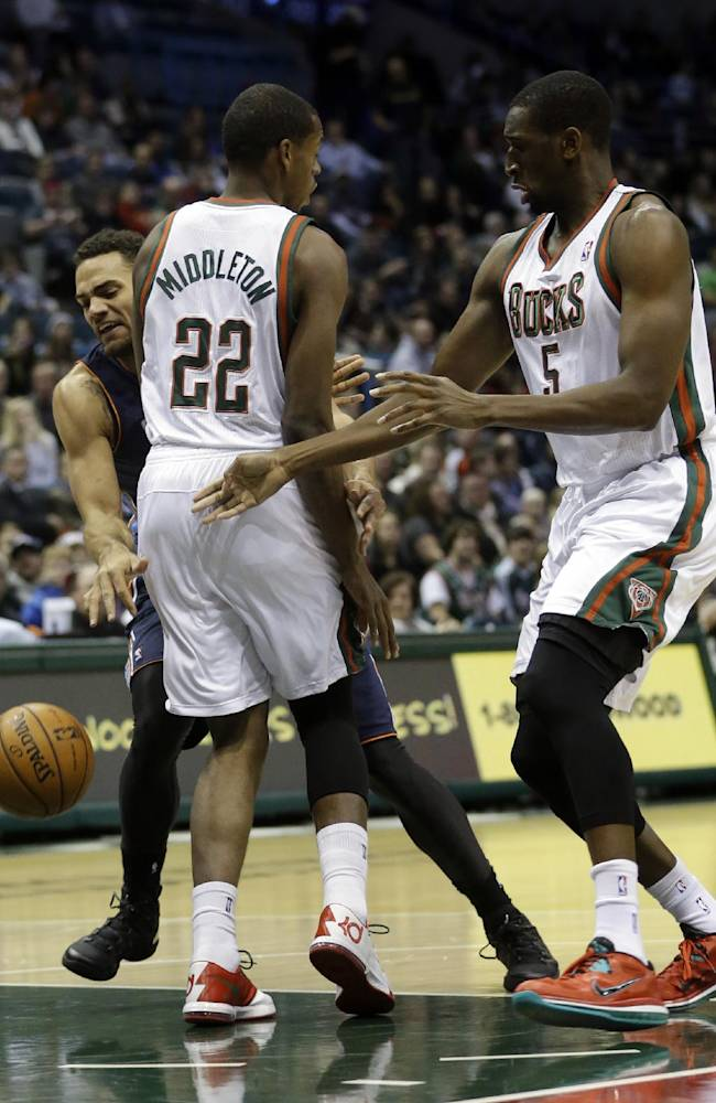 Charlotte Bobcats' Jeff Taylor loses the ball as he runs into Milwaukee Bucks' Khris Middleton (22) and Ekpe Udoh (5) during the first half of an NBA basketball game on Saturday, Nov. 23, 2013, in Milwaukee