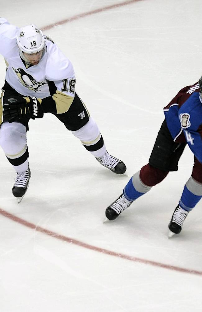 Pittsburgh Penguins left wing James Neal, left, pursues Colorado Avalanche defenseman Tyson Barrie during the first period of an NHL hockey game Sunday, April 6, 2014, in Denver