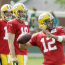 Green Bay Packers' Scott Tolzien, left, and Matt Flynn watch Aaron Rodgers throw during NFL football training camp Monday, July 28, 2014, in Green Bay, Wis. (AP Photo/Morry Gash)