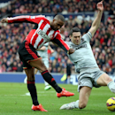 Sunderland's Jermain Defoe, left, vies for the ball with Burnley's captain Jason Shackell, right, during their English Premier League soccer match between Sunderland and Burnley at the Stadium of Light, Sunderland, England, Saturday, Jan. 31, 2015