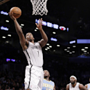 Brooklyn Nets guard Joe Johnson (7) goes up for a layup as Denver Nuggets point guard Nate Robinson (10) stands by from the floor in the first half of an NBA basketball game Tuesday, Dec. 3, 2013, in New York The Associated Press