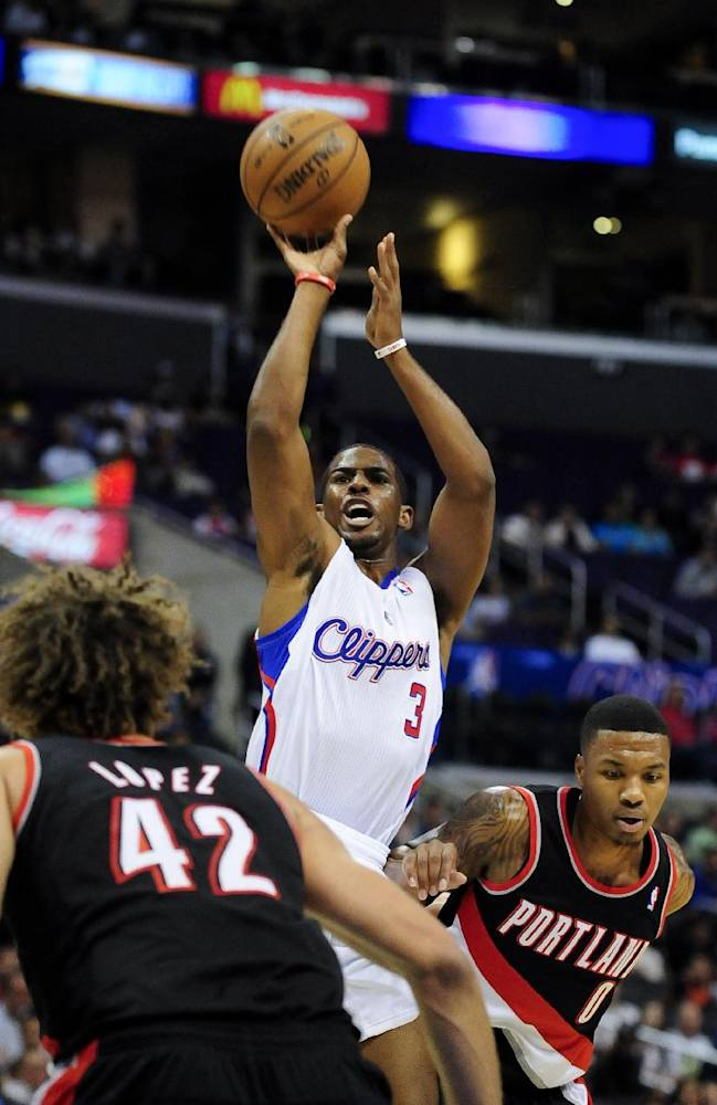 Los Angeles Clippers point guard Chris Paul (3) gets by Portland Trail Blazers point guard Damian Lillard (0) as he shoots over center Robin Lopez (42) in the first half of a preseason NBA basketball game, Friday, Oct. 18, 2013, in Los Angeles