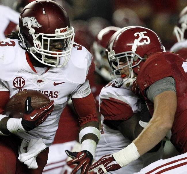 In this Oct. 19, 2013, file photo, Arkansas running back Alex Collins (3) tries to get around Alabama linebacker Dillon Lee (25) as he carries the ball during the second half of an NCAA college football game in Tuscaloosa, Ala. The next time you turn on the television and see a couple of sub-.500 teams slogging along, desperately hoping to just get bowl eligible, don't turn it off. There is bound to be at least a few players out there worth watching