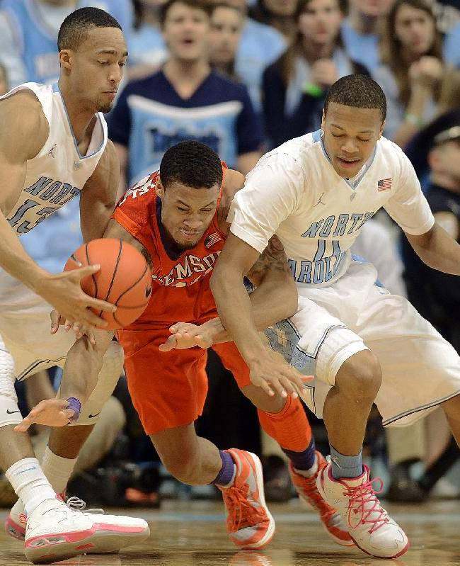 North Carolina's J.P. Tokoto and Nate Britt battle Clemson's K.J. McDaniels, center, for a loose ball during an NCAA college basketball game on Sunday, Jan. 26, 2014, in Chapel Hill, N.C