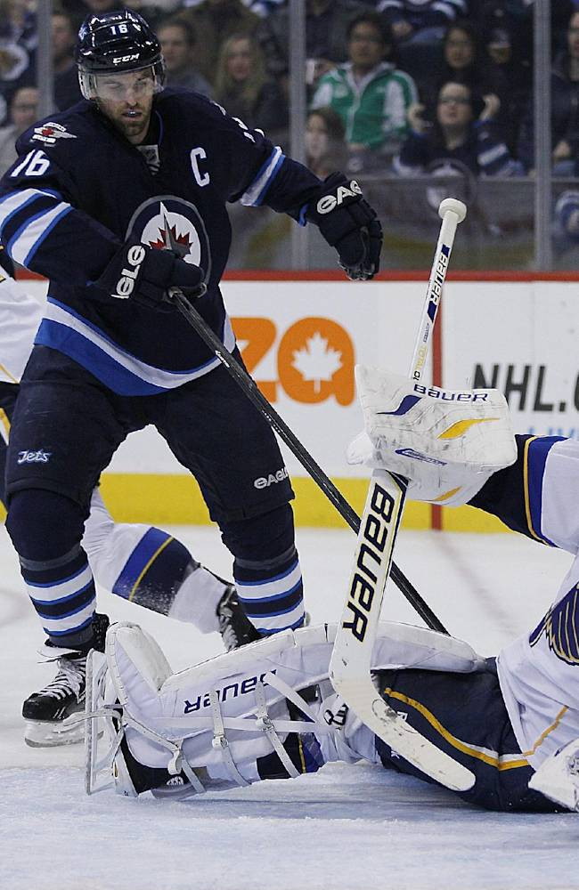 St. Louis Blues goaltender Brian Elliot gets tangled in Winnipeg Jets' Andrew Ladd (16) stick during the second period of an NHL hockey game, Friday, Oct. 18, 2013 in Winnipeg, Manitoba