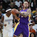 Los Angeles Lakers center Robert Sacre, back, pulls in loose ball in front of Denver Nuggets guard Ty Lawson in the first quarter of an NBA basketball game in Denver on Friday, March 7, 2014 The Associated Press