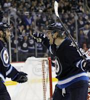 Winnipeg Jets' Andrew Ladd, left,and Bryan Little (18) celebrate after Little scored past Washington Capitals' goaltender Braden Holtby (70) during the second period of an NHL hockey game in Winnipeg, Manitoba, Tuesday, Oct. 22, 2013. (AP Photo/The Canadian Press, Trevor Hagan)