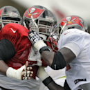 Tampa Bay Buccaneers defensive tackle Gerald McCoy, left, battles with tackle Anthony Collins during seven-on-seven drills at an NFL football training camp Sunday, Aug. 10, 2014, in Tampa, Fla The Associated Press