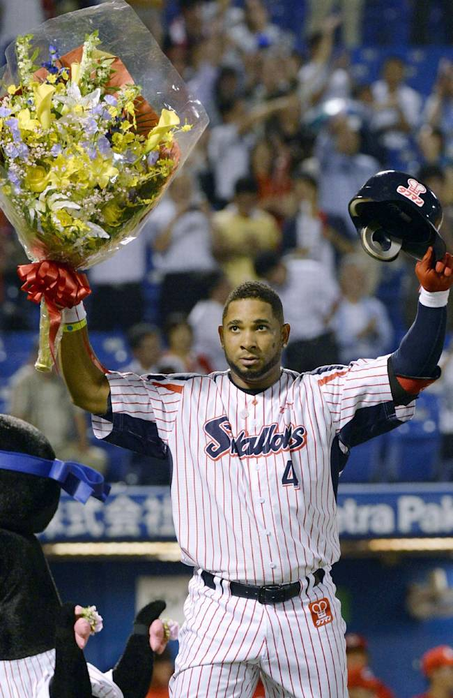 Yakult Swallows' Wladimir Balentien holds up a bouquet of flowers and his helmet as he celebrates with fans after hitting his 55th home run of the season in ar regular season game against Hiroshima Carp at Jingu Stadium in Tokyo Wednesday, Sept. 11, 2013. Former major leaguer Balentien matched Japan record set by Sadaharu Oh in 1964 and equaled by ex-major leaguers Tuffy Rhodes in 2001 and Alex Cabrera in 2002