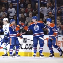 Vancouver Canucks' David Booth (7) skates past as Edmonton Oilers' Jordan Eberle (14), Jeff Petry (2) and Ryan Nugent-Hopkins (93) celebrate a goal during first period NHL hockey action in Edmonton, Alberta, on Saturday April 12, 2014 The Associated Press