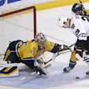 Nashville Predators goalie Pekka Rinne (35), of Finland, dives for the puck as Chicago Blackhawks left wing Bryan Bickell (29) and Predators defenseman Ryan Ellis (4) watch for the rebound during the first period of an NHL hockey game Saturday, April 12,