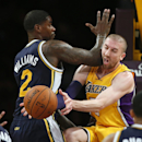 Los Angeles Lakers' Steve Blake, right, takes an elbow in the face from Utah Jazz's Marvin Williams, right, as he passes the ball of to Jordan Hill during the first half of an NBA basketball game in Los Angeles, Tuesday, Feb. 11, 2014 The Associated Press