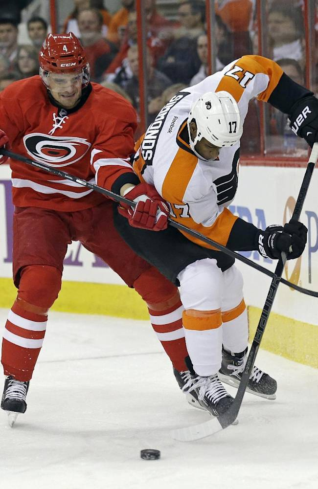 Carolina Hurricanes' Andrej Sekera (4), of Slovakia, and Philadelphia Flyers' Wayne Simmonds (17) struggle for possession of the puck during the first period of an NHL hockey game in Raleigh, N.C., Tuesday, Nov. 5, 2013