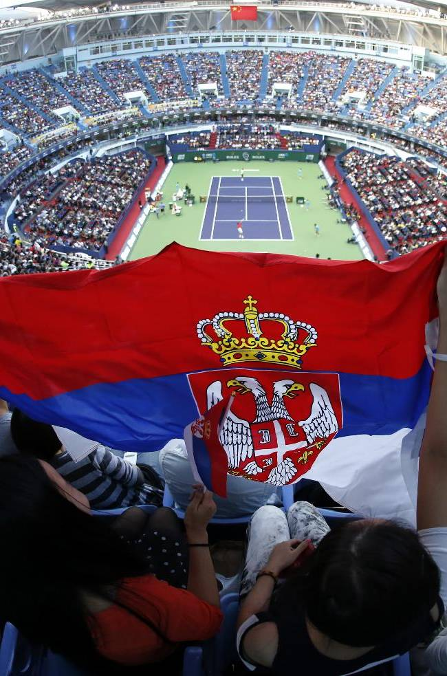 Fans of Serbia's Novak Djokovic cheer before the singles final match between Djokovic and Juan Martin del Potro of Argentina starts at the Shanghai Masters tennis tournament at Qizhong Forest Sports City Tennis Center, in Shanghai, China, Sunday, Oct. 13, 2013