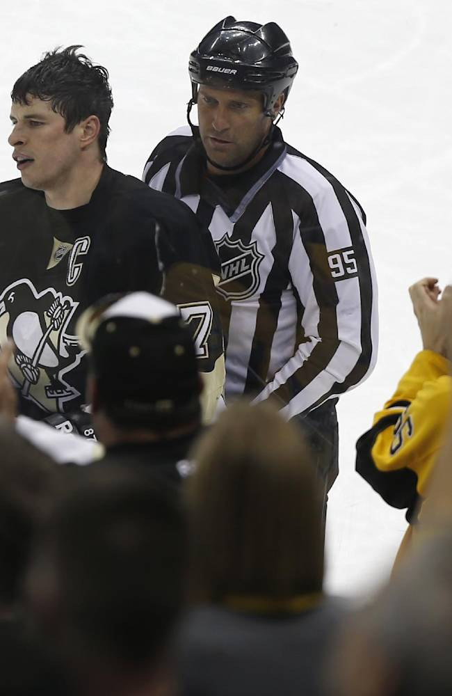 Fans applaud as Pittsburgh Penguins' Sidney Crosby is escorted to the penalty box after being penalized 2 minutes for roughing during the third period of an NHL hockey game against the Carolina Hurricanes on Tuesday, April 1, 2014, in Pittsburgh. The Hurricanes won 4-1