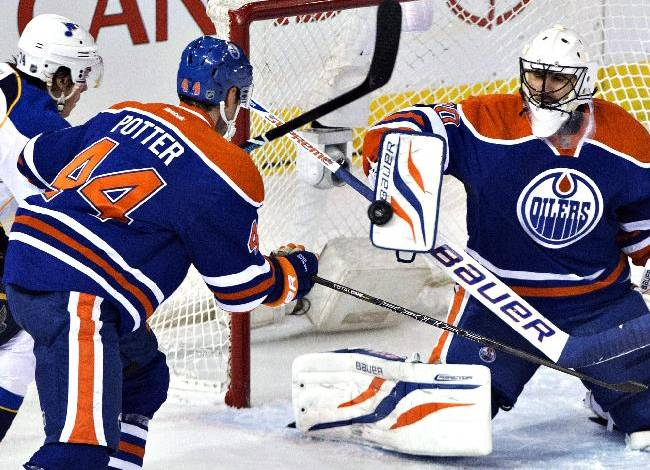 St. Louis Blues' T.J. Oshie (74) and Edmonton Oilers' Corey Potter (44) look for the rebound as Oilers goalie Ilya Bryzgalov (80) makes the save during the second period of an NHL hockey game in Edmonton, Alberta, on Saturday, Dec. 21, 2013