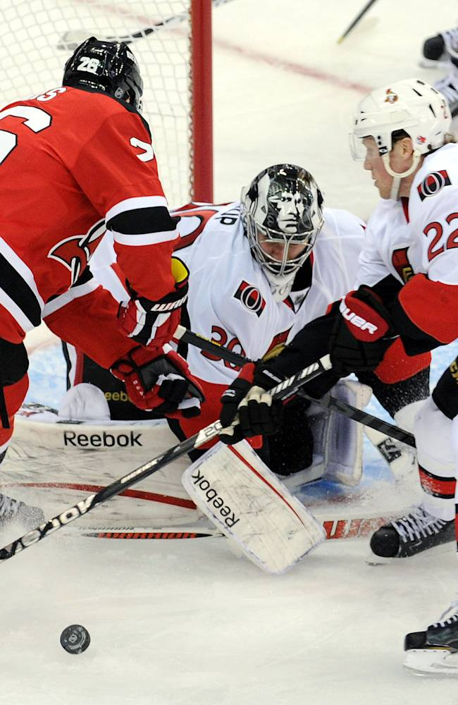 Ottawa Senators goaltender Ben Bishop makes a save as New Jersey Devils' Patrik Elias, left, of the Czech Republic, vies for the puck with Senators' Erik Condra, right, during the second period of an NHL hockey game Monday, Feb. 18, 2013, in Newark, N.J. (AP Photo/Bill Kostroun)