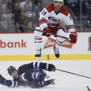 10ThingstoSeeSports - Carolina Hurricanes' Patrick Dwyer (39) leaps over Winnipeg Jets' Matt Halischuk during the second period of an NHL hockey game, Saturday, March 22, 2014, in Winnipeg, Manitoba The Associated Press