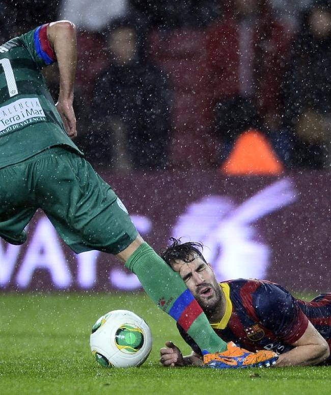 FC Barcelona's Cesc Fabregas, right, duels for the ball against Elche's Lamarasa during a Copa del Rey soccer match at the Camp Nou stadium in Barcelona, Spain, Wednesday, Jan. 29, 2014