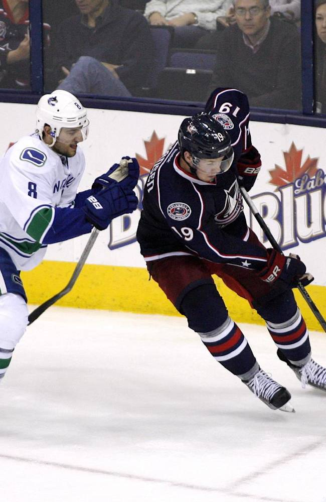 Columbus' Ryan Johansen, right, moves to score as Vancouver's Christopher Tanev closes in during the third period of an NHL hockey game, Sunday Oct. 20, 2013, in Columbus, Ohio
