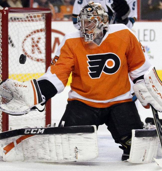 Philadelphia Flyers goalie Steve Mason reaches for the puck during the first period of an NHL hockey game against the San Jose Sharks, Thursday, Feb. 27, 2014, in Philadelphia