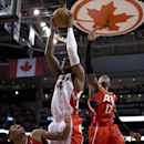 Toronto Raptors forward Patrick Patterson (54) rebounds against Atlanta Hawks guards Jeff Teague (0) and Dennis Schroder (17) during fourth-quarter NBA basketball game action in Toronto, Wednesday, Feb. 12, 2014 The Associated Press