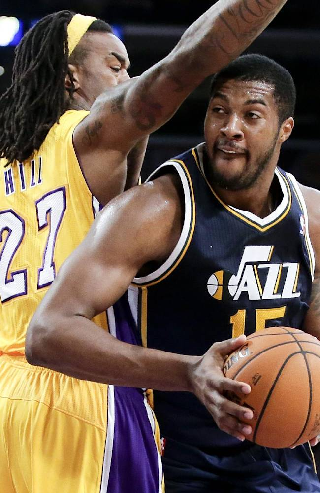 Utah Jazz forward Derrick Favors, right, drives to the basket around Los Angeles Lakers center Jordan Hill during the first half of a preseason NBA basketball game in Los Angeles, Tuesday, Oct. 22, 2013